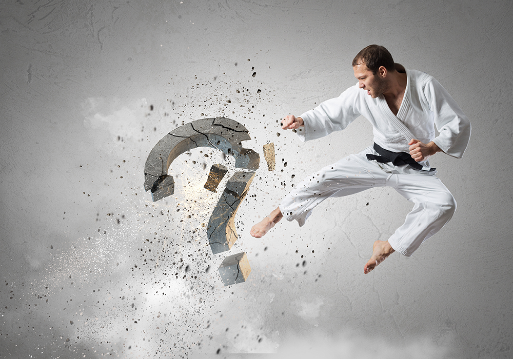 Young determined karate man breaking with leg concrete question sign