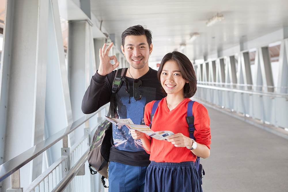 younger asian traveling man and woman standing with toothy smiling face sigh all right by okay hand sue for modern people backpacker traveling lifestyle