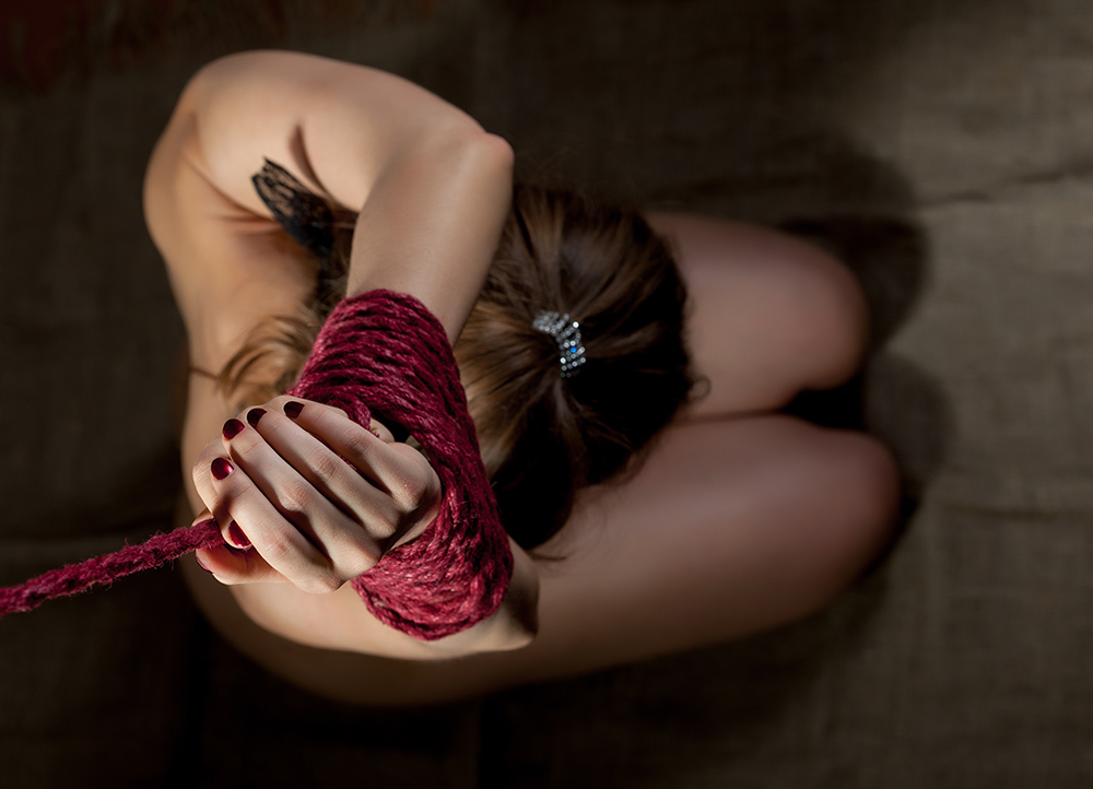 Top view of woman's hands bound with red rope, close-up