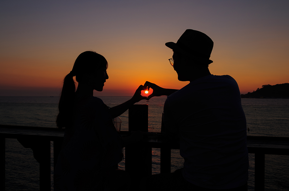 Silhouette of happy young couple making a heart shape with their hands in beautiful sunset.