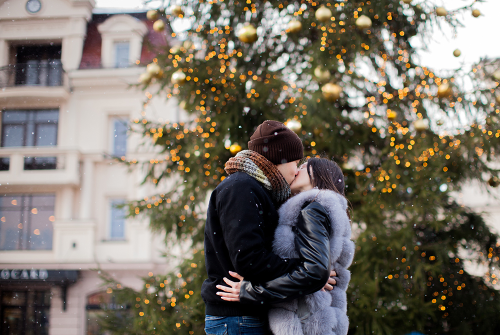 Loving couple kissing under snowfall on the background of the fir tree